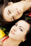 Dos muchachas hermosas que mienten en la hierba. Fotos de archivo