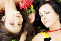 Dos muchachas hermosas que mienten en la hierba. Foto de archivo libre de regalías