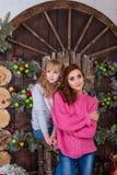 Dos muchachas hermosas que presentan en decoraciones de la Navidad Fotos de archivo libres de regalías