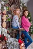 Dos muchachas hermosas que presentan en decoraciones de la Navidad Foto de archivo libre de regalías