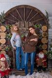 Dos muchachas hermosas que presentan en decoraciones de la Navidad Imagen de archivo libre de regalías