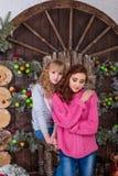 Dos muchachas hermosas que presentan en decoraciones de la Navidad Foto de archivo
