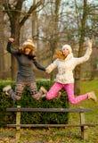 Dos muchachas hermosas que saltan del banco Fotos de archivo libres de regalías