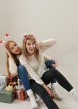 Dos muchachas hermosas que se divierten en el trineo viejo del vintage con los regalos FO Imagenes de archivo