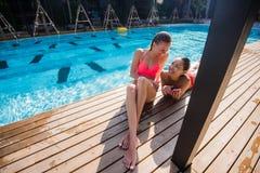 Dos muchachas hermosas que toman un selfie al lado de piscina Fotos de archivo libres de regalías