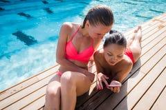 Dos muchachas hermosas que toman un selfie al lado de piscina Foto de archivo libre de regalías