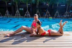 Dos muchachas hermosas que toman un selfie al lado de piscina Imagenes de archivo