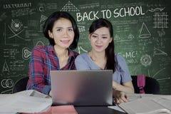 Dos muchachas hermosas que usan un ordenador portátil en la sala de clase Foto de archivo libre de regalías