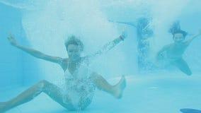 Dos muchachas hermosas rubias y morenita que salta en el agua y que se divierte almacen de metraje de vídeo