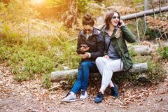 Dos muchachas hermosas sentadas abajo en el bosque Fotos de archivo libres de regalías