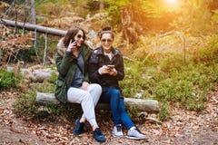 Dos muchachas hermosas sentadas abajo en el bosque Foto de archivo