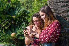 Dos muchachas hermosas son de risa y que se ríen alguien foto de archivo