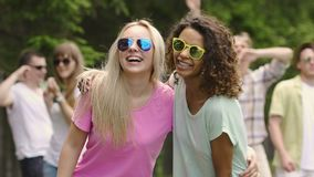 Dos muchachas hermosas sonrisa, bailando con los amigos en el partido, forma de vida sana almacen de video