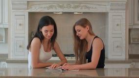 Dos muchachas hojean a través de una revista en la cocina metrajes