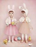 Dos muchachas, huevos de Pascua y pollos Imagenes de archivo