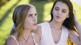 Dos muchachas increíbles queitly se sientan en el banco, hablan, ríen, compartiendo pensamientos y chisme el la tarde del verano almacen de metraje de vídeo