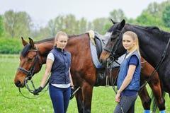Dos muchachas - jinetes de la doma con los caballos Foto de archivo libre de regalías