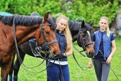 Dos muchachas - jinetes de la doma con los caballos Imagen de archivo libre de regalías