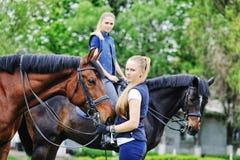Dos muchachas - jinetes de la doma con los caballos Fotografía de archivo libre de regalías