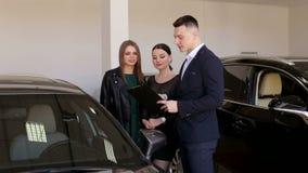 Dos muchachas jovenes de la moda hablan con un ayudante de las ventas en una tienda del coche Compra de un coche almacen de metraje de vídeo
