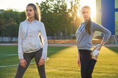 Dos muchachas jovenes de los deportes que hacen la gimnasia por la mañana en la hierba verde aire abierto, amanecer, aptitud, sal Foto de archivo
