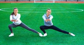 Dos muchachas jovenes de los deportes que hacen la gimnasia por la mañana en la hierba verde aire abierto, amanecer, aptitud, sal Fotos de archivo