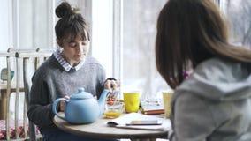 Dos muchachas jovenes del estudiante universitario que comen en un café y que hablan, lado almacen de video