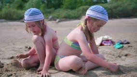 Dos muchachas juegan en la playa que hace figuras de la arena Día de verano caliente Días de fiesta de la familia por el mar imágenes de archivo libres de regalías