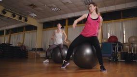 Dos muchachas juntos hacen ejercicios del deporte con las bolas de la aptitud en el cuarto aerobio Pilates metrajes