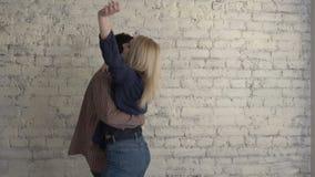 Dos muchachas lesbianas jovenes que bailan contra una pared blanca ladrillosa, pares felices, concepto de familia del lgbt, amant almacen de video