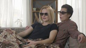 Dos muchachas lesbianas jovenes se están sentando en el sofá, cubierto en una manta caliente, mirando la película 3d, usando el t almacen de metraje de vídeo