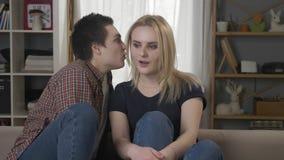 Dos muchachas lesbianas jovenes se están sentando en el sofá, una muchacha con el pelo corto dice la secreción a su socio, el blo almacen de metraje de vídeo