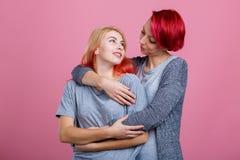 Dos muchachas lesbianas, se abrazan y miran en uno a En un fondo rosado Fotografía de archivo libre de regalías