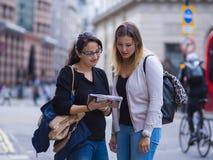 Dos muchachas leyeron un mapa en el centro de ciudad de Londres Fotografía de archivo