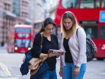 Dos muchachas leyeron un mapa en el centro de ciudad de Londres Imagen de archivo