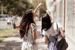 Dos muchachas lindas amistosas con el pelo oscuro largo, el equipo casual que lleva, paseo abajo de la calle y llevar a cabo las  foto de archivo libre de regalías