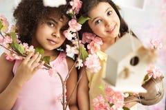 Dos muchachas lindas con las flores rosadas Fotografía de archivo