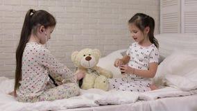 Dos muchachas lindas de los niños que juegan al doctor con el oso de peluche metrajes