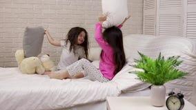 Dos muchachas lindas de los ni?os que juegan en el dormitorio almacen de video