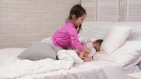 Dos muchachas lindas de los ni?os que juegan en el dormitorio almacen de metraje de vídeo