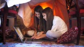 Dos muchachas lindas en los pijamas que se sientan con el ordenador portátil en la tienda hecha de mantas Fotografía de archivo libre de regalías