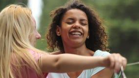 Dos muchachas lindas que hacen danza se mueven, abrazando uno otro en el partido al aire libre metrajes