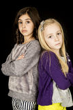 Dos muchachas lindas que se colocaban con sus brazos doblaron la sonrisa Imagen de archivo libre de regalías