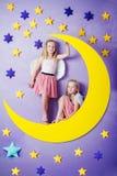 Dos muchachas lindas que se sientan en una luna grande Imagen de archivo libre de regalías