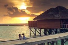 Dos muchachas miran la puesta del sol en maidives imagenes de archivo