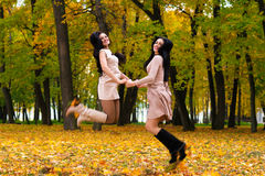 Dos muchachas morenas hermosas que saltan el otoño del fondo parquean Imagen de archivo
