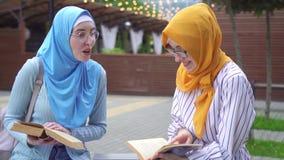 Dos muchachas musulmanes sonrientes positivas en el hijab y los libros de lectura elegantes de los estudiantes de los vidrios que almacen de metraje de vídeo