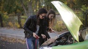 Dos muchachas no demasiado brillantes que intentan recargar una batería de coche muerta Dos muchachas en la capilla abierta de un almacen de video