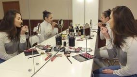 Dos muchachas pintan los labios delante del espejo metrajes