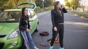 Dos muchachas pueden el ` t tienen un coche y están intentando entender el fracaso Las muchachas llaman en asistencia técnica en  metrajes